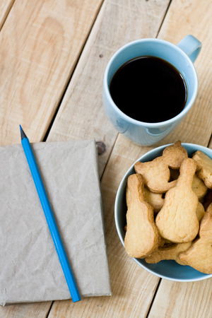 unpainted: Sweet tasty cookies in the blue plate, a cup of black coffee and notebook on wooden unpainted background.