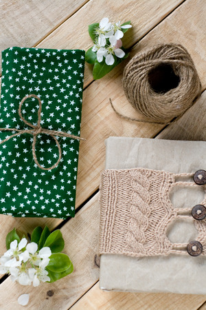 skein: Old vintage notepad knitted in beige sweater, thick skein of yarn, cloth, flower pear lying on unpainted wooden background.