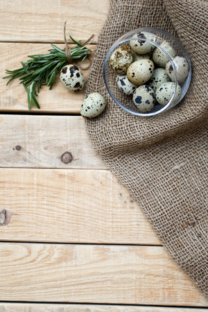 unpainted: Quail eggs a bunch of rosemary and burlap are on the unpainted wooden background