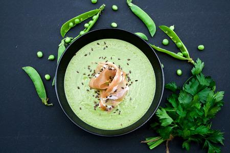 perejil: Sopa verde saludable con jamón y guisantes en un fondo negro Foto de archivo