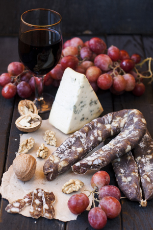 dry sausage: Snacks for wine, cheese with mold, pink grapes, walnuts and jerked dry sausage