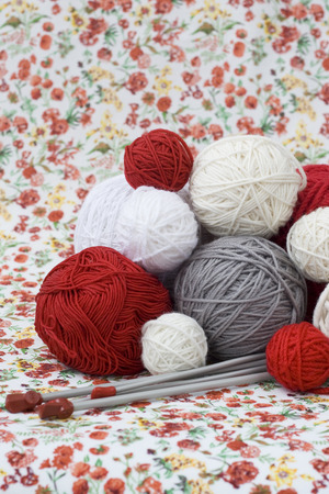 A lot of bright balls of knitting on the background of a red flower Reklamní fotografie