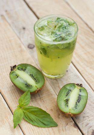 Cocktail with kiwi and basil in a glass on a wooden background.