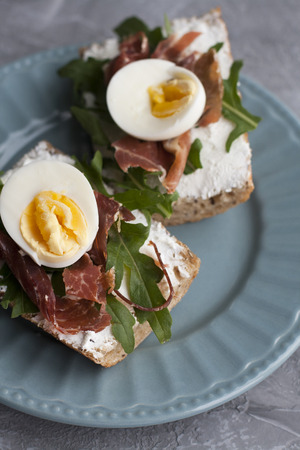 Sandwiches with whole grain bread, homemade cheese, arugula, ham and egg. Healthy snack. Reklamní fotografie