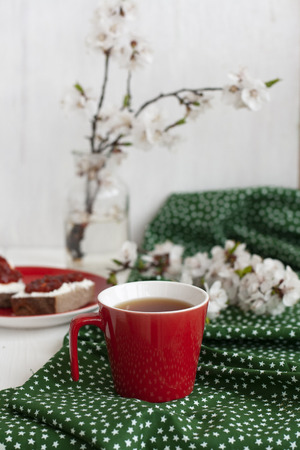 A cup of black tea on a green napkin, homemade rye bread with soft cream cheese and smoky dried tomatoes, a glass vase of apricot bloom on the white background. Фото со стока
