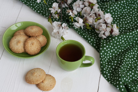 A cup of black tea on a green napkin, homemade cookies, a branch of apricot bloom on the white background. Stok Fotoğraf