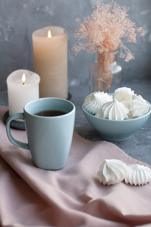 A hot cup of black tea with a bowl of airy meringues on a pink tablecloth, wax candles, a glass vase with decorative herbs on a gray background.