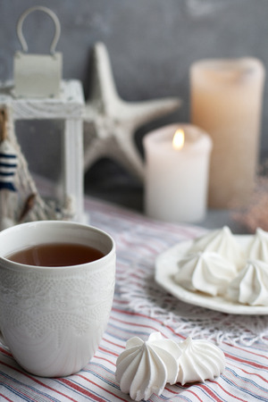 A hot cup of black tea with a plate of airy meringues on a striped tablecloth, decorative starfish and lantern, wax candles, decorative herbs on a gray background.