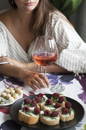 A beautiful woman with glass of wine at the restaurant, romantic dinner, a plate of fragrant baguette slices with arugula and raspberry, a plate of olive and mozzarella canapes, roquefort cheese.