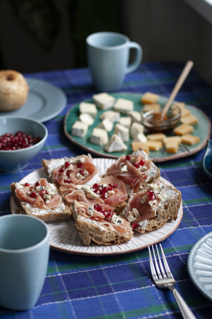 A nutritious and tasty breakfast for two: baked apples, baguette slices with smoky salmon and soft cream cheese; a plate of camambert and cheddar cheese slices with small bowl of honey, a half of pomegrenate, a cup of coffee. A checkered blue tablecloth background.