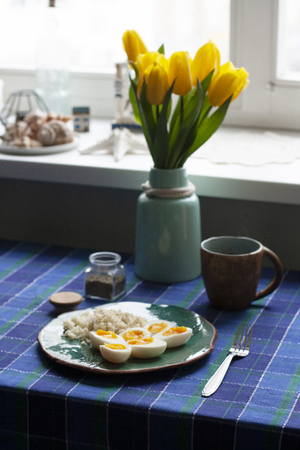 A healthy and nutritious breakfast: a cup of tea; a plate of hardboilde eggs with cuscus. A tulip bouquet in a vase, a checkered tablecloth, a window sill with decorative seashells and starfish on sunny background.