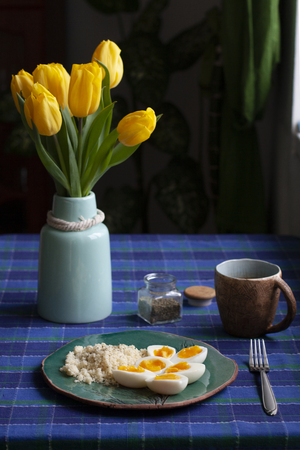 A healthy and nutritious breakfast: a cup of tea; a plate of hardboilde eggs with cuscus. A tulip bouquet in a vase, a checkered tablecloth on a shaded background.