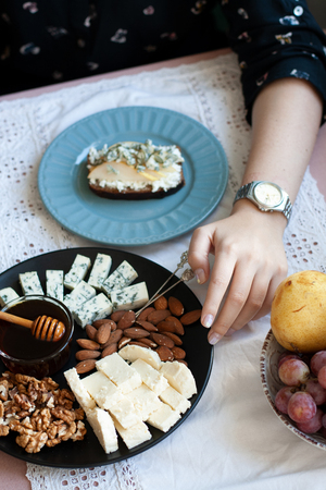 A gourmet lunch: a black plate of appetizers on a white tablecloth: walnuts, almonds, cheese, roquefort cheese, a small bowl of honey, a slice of rye bread with roquefort and cream cheese, a bowl of sweet juicy fruits. A white tablecloth background.