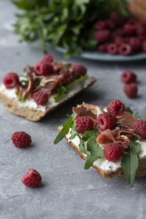 A nutritious and healthy breakfast: bread slices with aragula, raspberry, cream cheese and pastrami; a plate of aragula, bread and raspberries on the gray background.
