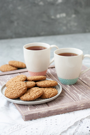 A tasty snack: two cups of black tea and a plate of oatmeal cookies; a wooden board on the gray background.