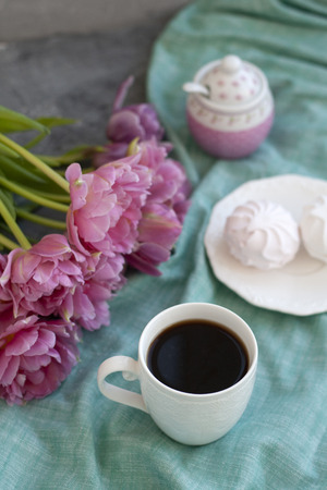 A tasty snack: a cup of black coffee, a plate of zefirs; a sugar-bowl on a green talecloth; a bouquet of pink flowers on a gray background.