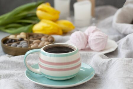 A tasty snack: a cup of dark coffee, a plate of fluffy zephyr and a box assorted of sweets; wax candles on the white tablecloth, a bouquet of yellow tulips on the gray background. Banque d'images