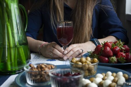 A gourmet break: a plate of strawberries, small bowls of cranberries, olives and walnuts, mozzarella and olive canapes, a glass of grape juice; a vase with flowers on a blue tablecloth.