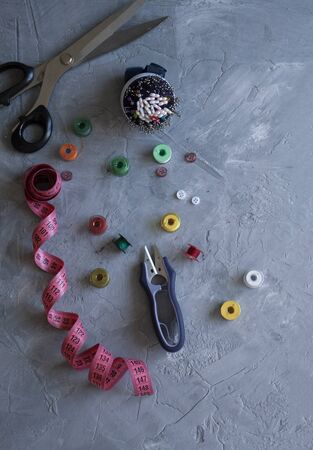 A sempstress inventory: measure tape, buttons, needles, threads and scissors on a gray background. Stok Fotoğraf