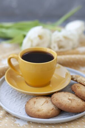 A tasty treat: a cup of black coffee and a plate of homemade cookies on a golden tablecloth; a bouquet of white roses on a gray background.