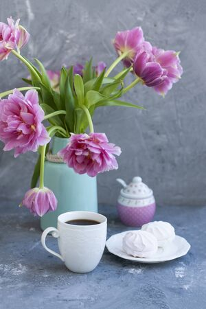 A tasty treat: a cup of black coffee and a plate of fluffy marshmallows; a sugar bowl and a vase with flowers on a gray background.