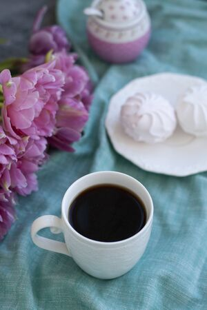 A tasty treat: a cup of black coffee and a plate of fluffy marshmallows; a sugar bowl on a teal tablecloth and a vase with flowers on a gray background.