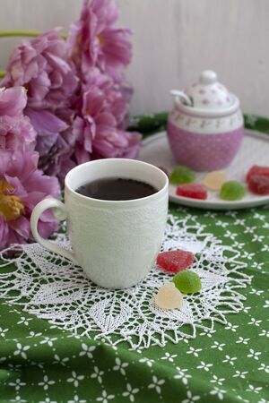 A tasty treat: a cup of black tea and a plate of fruit jellies; a sugar bowl and a bouquet of flowers on a green tablecloth.