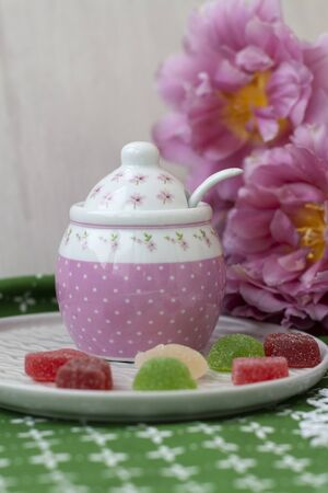 A tasty treat: a plate of fruit jellies of different colors; a sugar bowl and a bouquet of flowers on a green tablecloth.