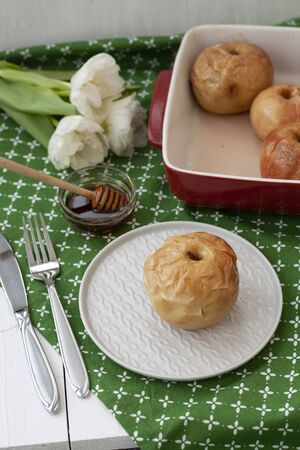 A healthy lunch: baked apples with a bowl of honey on side; a bouquet of a white flowers on a green tablecloth.