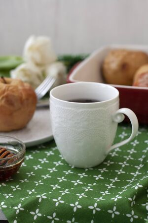 A healthy lunch: a cup of black tea with baked apples with a bowl of honey on side; a bouquet of a white flowers on a green tablecloth.