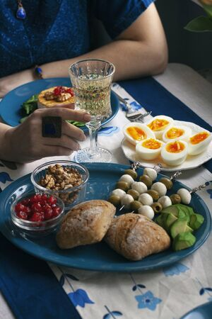 A gourmet dinner: a plate of grilled camembert with spinach, walnuts and smoky tomatoes, various appetizers and a glass of wine on a decorative tablecloth.