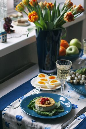 A gourmet dinner: a plate of grilled camembert with spinach, walnuts and smoky tomatoes, various appetizers and a glass of wine; a bouquet of tulips in a vase on a decorative tablecloth.