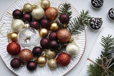 Christmas colored decorations lie on a white plate along with the branches of the Christmas tree. A white napkin and candles stand nearby. Stock Photo
