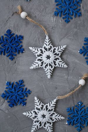 Two white ornaments on a Christmas tree in the form of snowflakes and many blue snowflakes lie on a gray concrete background.