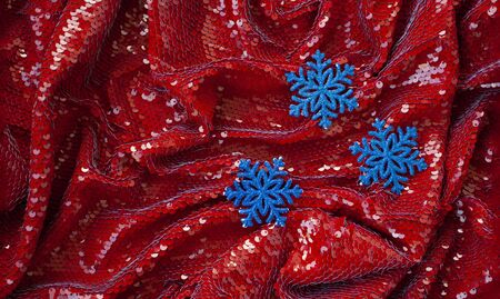 Red festive background with glitter and three blue decorations for Christmas tree for lettering and greeting card