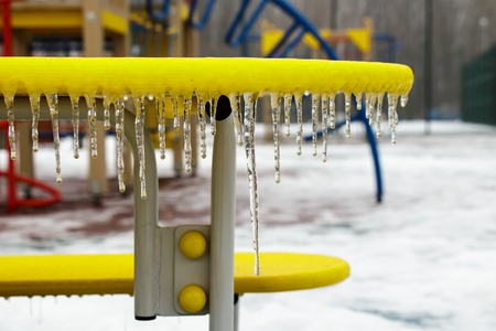 winter playground with a bench covered with ice games Stock Photo