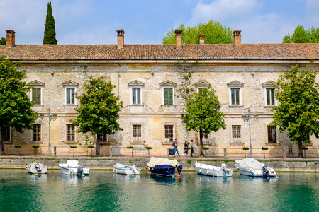 PESCHIERA DEL GARDA, ITALY - MAY 1, 2015: Boats parked at the river Mincio in front a building in Peschiera, a village of Garda Lake, and belong to the province of Verona, in Veneto, Italy. Editorial