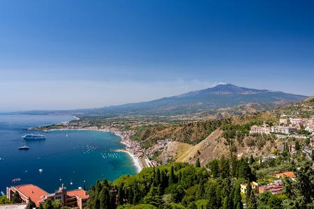 タオルミーナ、シチリア、イタリアのギリシャの劇場から見た背景にエトナ火山と夏の日にタオルミーナ湾 報道画像
