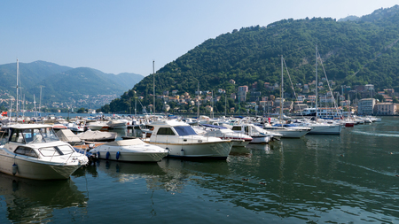 Boats moored on Lake Como with the mountains in the background, Italy Stock Photo
