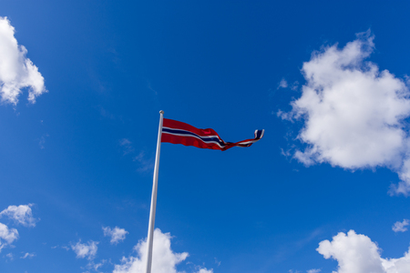 Norwegian flag waving on blue sky and white clouds
