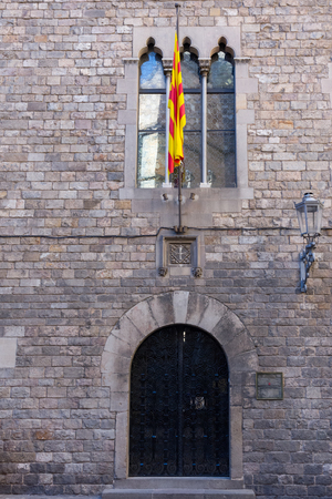 Main entrance of an ancient palace, with a flag, in the center of Barcelona. Spain. Redactioneel