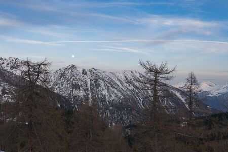 Snowy panorama of the Val Bognanco that opens behind Domodossola, in background the moon Piedmont, Italy Stockfoto