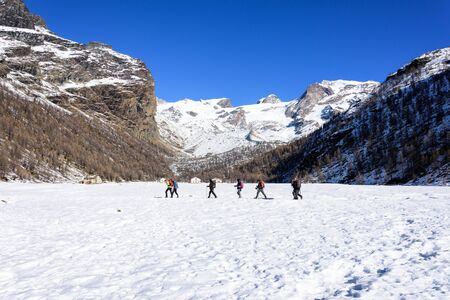 Group of hikers trekking in the mountains of the Alps. The trekkers are going through a snowy landscape. Italy Stockfoto