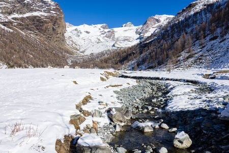 Mountain stream makes its way through melting snow, in background refuge in the Val dAyas, Valle dAosta. Italy Stockfoto