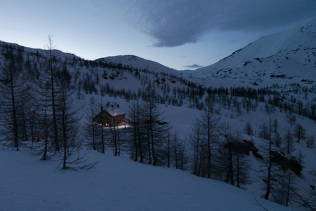 mountain refuge illuminated in the darkness of a snowy landscape, italy