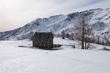 stone mountain refuge in a snowy landscape, italy Redactioneel