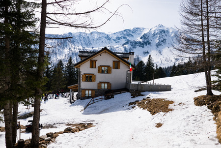 Excursions make a stop at a mountain refuge with the Italian flag in a snowy landscape, Italy