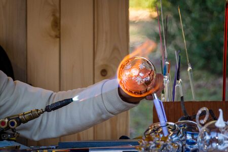 Glassblower handling the glass ball with a gas burner, italy