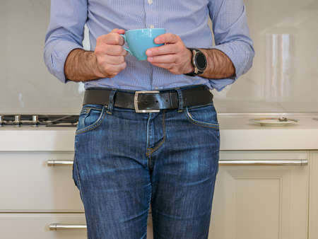 man drinks coffee in a colorful cup in the kitchen