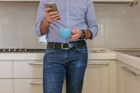man drinks a coffee in the kitchen and in the meantime looks at the smartphone